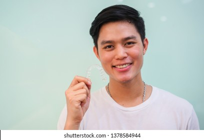 close up young asian man smiling with hand holding dental aligner retainer (invisible) at dental clinic for beautiful teeth treatment course concept