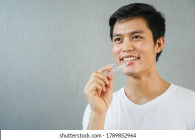close up young asian man smiling with hand holding dental aligner retainer (invisible) on gray background of dental clinic for beautiful teeth treatment course concept