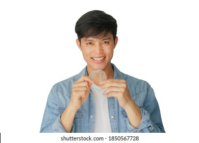 close up young asian man smiling with hand holding dental aligner retainer (invisible) isolated on white background for beautiful teeth treatment course and design ads banner concept