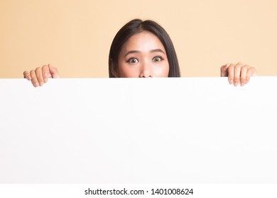Close up of young Asian woman behind a blank sign on  beige background