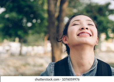 Close up young Asian woman face  in nature take a deep breath feeling fresh.
