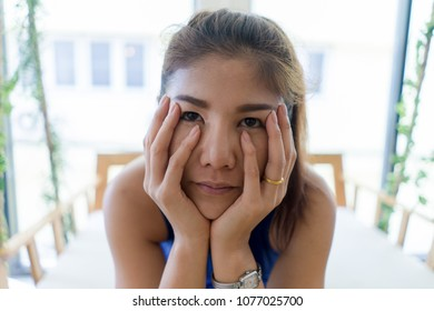 Close up Young Asian woman feeling bore looking through camera with hand cover face.