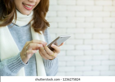 close up young asian woman hand holding smartphone and touching on screen devices for shopping online on website in living room at home , lifestyle concept