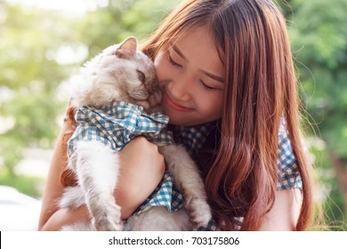 Close up of young Asian woman playing with her persian cat, human-animal relationships.