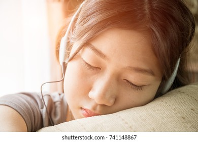 Close up young asian woman short hair listening music on the couch at home