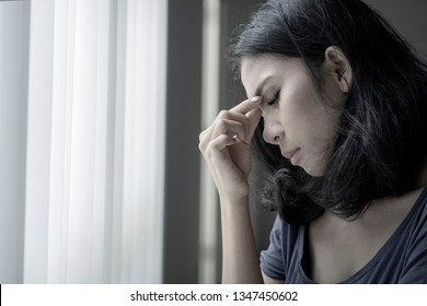 Close up of young Asian woman suffering headache near the window in black background