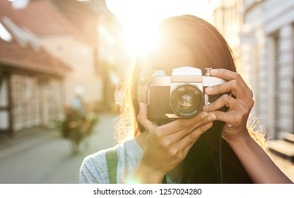 Close Up of young Asian woman taking photographs with a vintage slr camera while walking around the city in the afternoon