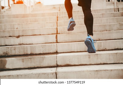 Close up of young athlete man running up the stairs with copy space