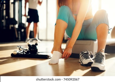 Close up of young athletic girl putting on socks and preparing for new exercise day in the gym.