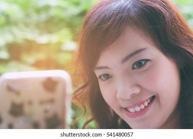 Close up of young attractive Asian woman using smartphone.