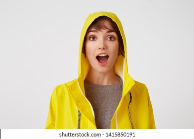 Close up of young attractive girl in a yellow raincoat with a surprised expression on her face, standing over white wall with wide open moth and eyed. Positive emotion concept.