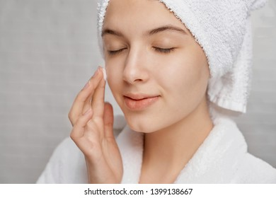 Close up of young, attractive woman with closed eyes applying moisturizer on face. Pretty girl with perfect skin in white bathrobe with white towel posing on grey background.