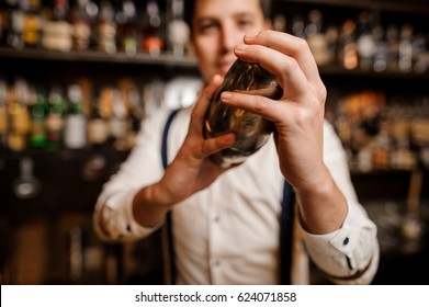 close up young barmans hands with shaker