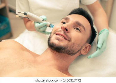 Close up of a young bearded man looking glad with modern tool near his face nourishing the skin