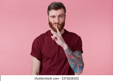 Close up of young bearded man with tattooed hand keeps fore finger on lips, demonstrates silence gesture, isolated over pink background with one rised with raised eyebrow.