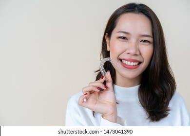 close up  young beautiful asian woman smiling with hand holding dental aligner retainer (invisible) at cream background of dental clinic for beautiful teeth treatment course concept