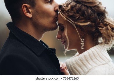 Close up of young beautiful couple of blonde bride and handsome groom posing outdoors at cold weather and kissing. Husband kissing beautiful wife in cheen, she smiling. Autumn wedding.
