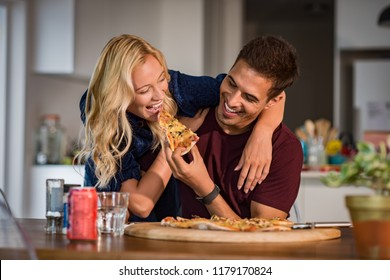 Close up of a young beautiful couple sharing pizza cut at home. Young man and happy woman sharing pizza and eating together. Handsome smiling man feeding his girlfriend with italian pizza.