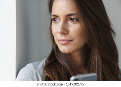 Close up of a young beautiful girl standing leaning on a gray wall over gray background, using mobile phone