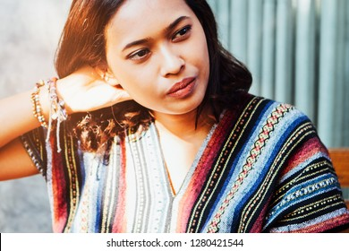 Close up young beautiful tan Asian woman with thoughtful face over gray concrete wall and house door, thinking for future and dream concept