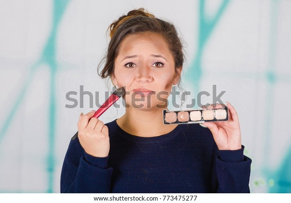 Close up of young beautiful woman holding a make up palette and doing crazy make-up in her face using a brush, in a blurred background