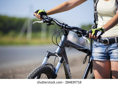 Close up of young beautiful woman riding a bicycle in a park
