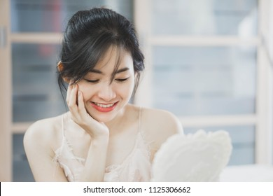 Close up of young beautiful women look into the mirror touching her face with natural smile. Beauty skin care concept.