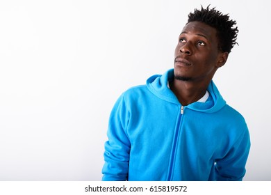 Close up of young black African man thinking while looking up against white background