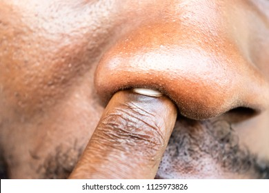 Close up of Young Black man is picking his nose. African Man making a finger gesture inside nose isolated for bad habit and hygiene concept