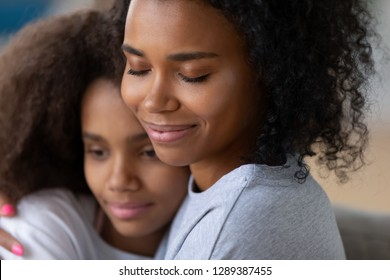 Close up of young black mother hugging teenage daughter, fell love and affection, caring African American mom hold teen girl in arms, embracing, having intimate moment together as best friends