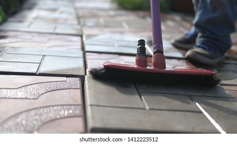 Close up of young boy helps family cleaning the tile using a mop in garden.