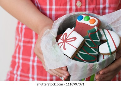 Close Up of Young Boy Offering Tin of Christmas Gingerbread Cookies as Gift