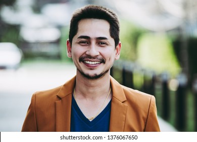 Close up young business handsome man smiling casual with happy outdoor on urban blur background, process color.