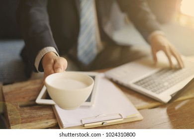 Close up young business man working during hand holding cup of coffee, smart work, coffee break
