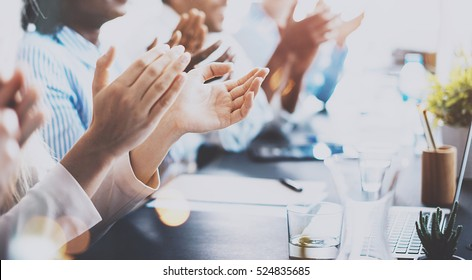 Close up of young business partners applauding to reporter after listening report at seminar. Professional education, work meeting, presentation or coaching concept.Horizontal,blurred background
