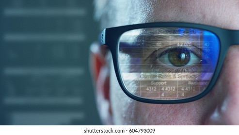Close up of young businessman with blue eyes wearing the glasses looking on the waveform lines expressed concept of stock market,augmented reality, technology, stock exchange  and finance