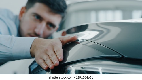 Close up young businessman checking anonymous just repaired in car auto body shop. Concept of auto deal, car dealerships, used cars, luxury cars