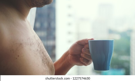 Close up of young businessman hand with a cup of coffee looks at city towers from a window.