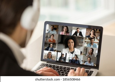 Close up young businessman in headphones holding online video call conference with african american female team leader and diverse colleagues using computer application, distant working communication. - Shutterstock ID 1856508466