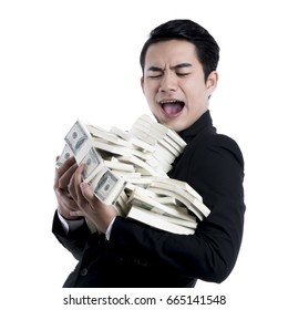 Close up the young businessman holding a large pile of dollars in his arms with so excited expression on white background