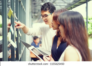 close up young businessman manager writing  sticky paper pad on glass wall for explain and discuss about work flow process with employee at loft modern co-space office, teamwork concept