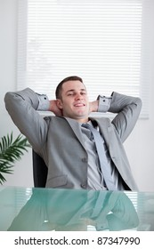 Close up of young businessman relaxing sitting behind a table
