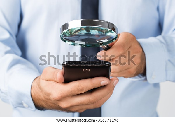 Close up of young businessman searching, spying the mobile, smart phone
