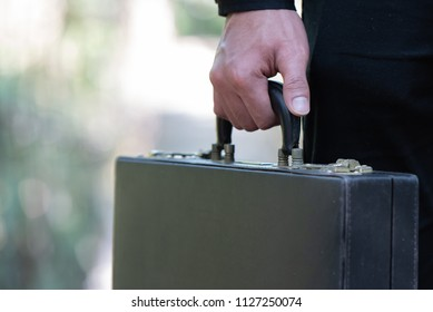 Close up of a young businessman walking and carrying briefcase in hand.