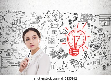 Close up of a young businesswoman holding a pen. She is standing near a concrete wall with a start up sketch and a large red light bulb icon