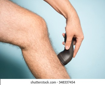 Close up of young Caucasian man shaving hair from legs