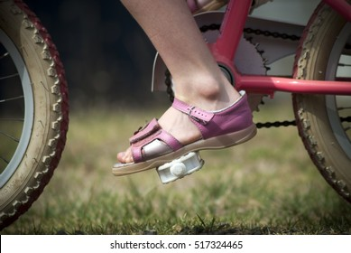 close up of a young child's foot on the pedal of a bike, riding outside