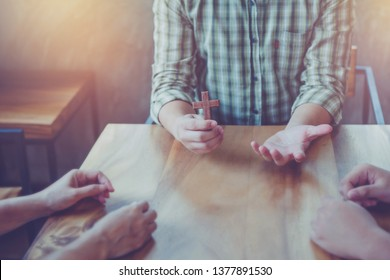 Close up of Young christian man holding small wooden cross in hands while explains about Jesus story and sharing gospel to his unbeliever friends around wood table indoor ,  great commission concept.
