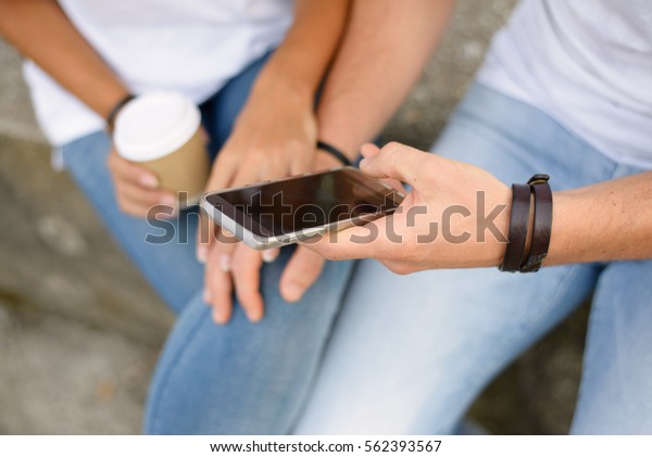 Close up of young couple dating and texting on smartphone. Man and woman holding cellphone.  Modern lovers relationship and technology use concept.