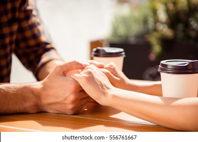 Close up of young couple holding each other hands in cafe